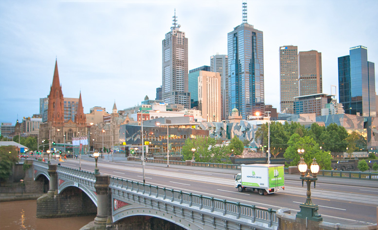 Melbourne removalist truck traveling over Flinders st bridge, ready to tackle apartment moves.